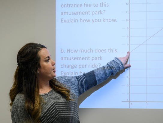 Math teacher Kendra Barrett reviews a math problem during a geometry class with junior and senior students at Gibson Southern High.