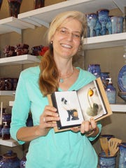 Corinna Zimmerman, owner of White Mountain Pottery in Ruidoso showing photos of ceramic sculpture she has completed.