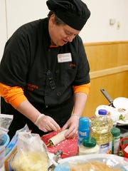 Jon Sterlace, a Cornell Cooperative Extension of Steuben County chef, creates a wrap Friday at the Locally-Grown Food Festival.