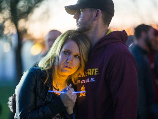 Kelly Bauer and Ryan Imming hug during a vigil for