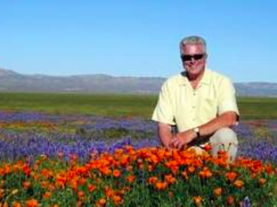 Television host Huell Howser poses for a photo at the Antelope Valley California Poppy Reserve in Lancster, Calif., on March 31, 2005.
