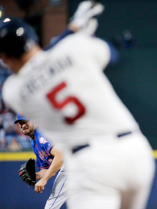 New York Mets starting pitcher Jonathon Niese, left, looks on as Atlanta Braves' Freddie Freeman hits a pitch to ground out in the first inning of a baseball game, Saturday, Sept. 20, 2014, in Atlanta. (AP Photo/David Goldman)