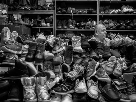 Jamn Dawod an Iraqi refugee sits among a pile of shoes that he has for sale at the Derby City Flea Market. June 2, 2018.