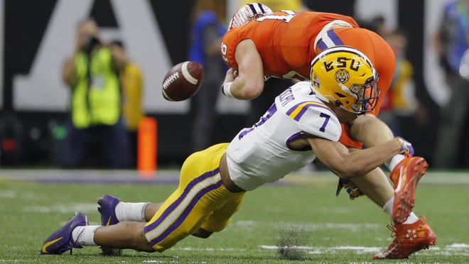 LSU safety Grant Delpit forces a fumble by Clemson quarterback Trevor Lawrence during the second half of a NCAA College Football Playoff national championship game Monday, Jan. 13, 2020, in New Orleans.