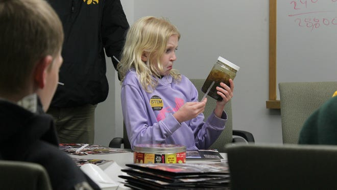 Margo Brinegar, 12, looks at a jar of goo illustrating the phlegm production of a smoker with chronic obstructive pulmonary disease during Junior Mini Medical School on Wednesday at the University of Iowa.