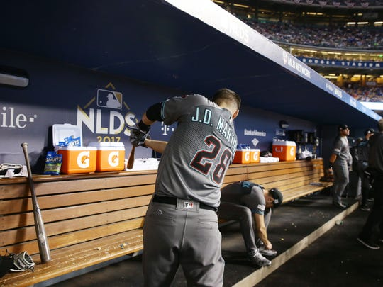 J.D. Martinez works on his swing in the dugout minutes before playing the Dodgers in Game 1 on Friday in Los Angeles.