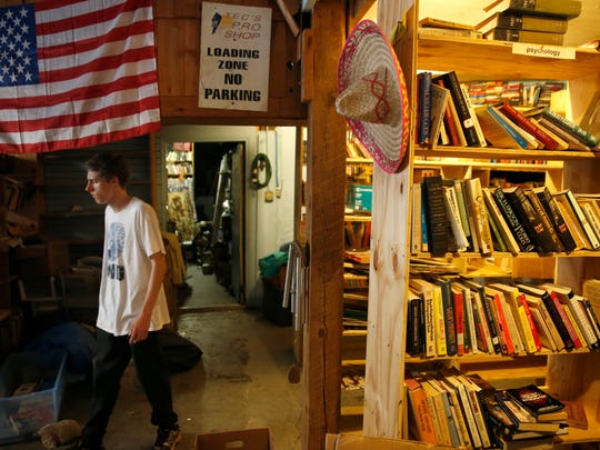 Michael Forest Hayes, son of Jayson Hayes who owns the International Book Mine on Gaines Street, works to organize the store with his father and brother on Friday, Sept. 11, 2015.