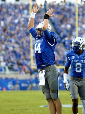 Kentucky's  Patrick Towles signals for the crowd to stay fired up after scoring a touchdown. Oct. 25, 2014