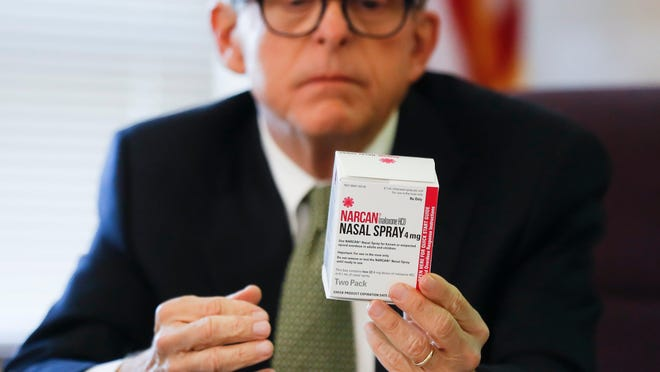 FILE - In this Sept. 7, 2017 file photo Gov. Mike DeWine, then Ohio Attorney General, handles a box of Narcan during a news conference to announce a program and pilot study in Hamilton County to more than quadruple distribution of the opioid overdose-reversing drug.