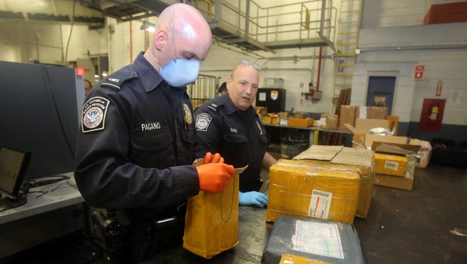 Customs and Border Protection officers checking mailed boxes at JFK airport.