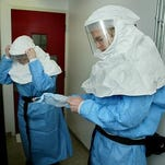 Microbiologists put on protective suits before entering a room where hazardous biological and chemical agents were handled at University Hygienic Laboratory in December of 2003. Officials requested their names not be used, citing security concerns.