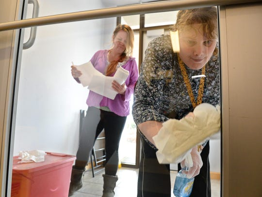 Brandy Sell, right, a client of Quality Life Concepts, cleans windows recently under the guidance of direct support professional Annette Kelly-Robinson.