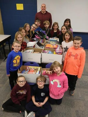 Nick Mahlstadt (top) poses with Wilder Elementary students and the school supplies they gathered to be sent to Ghana