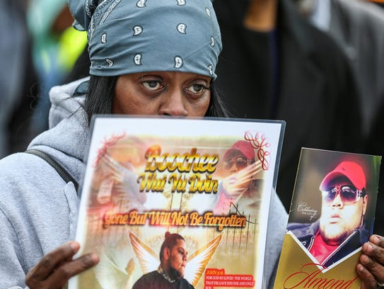 Damita Talley Boochee holds signs in memory of her