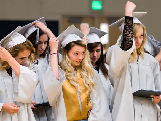 Graduating seniors move their tassels to the other