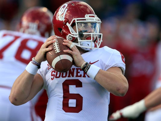 Oklahoma quarterback Baker Mayfield (6) looks for a receiver during the first half of an NCAA college football game against Kansas in Lawrence, Kan., Saturday, Nov. 18, 2017. (AP Photo/Orlin Wagner)