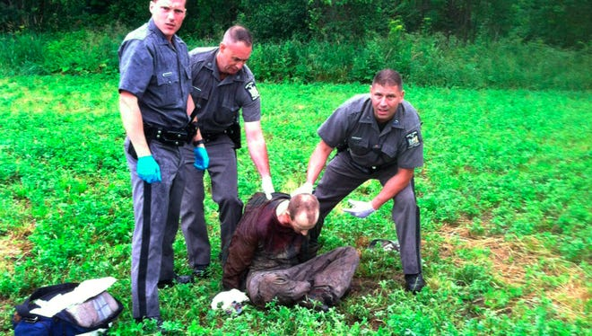 Police stand over David Sweat after he was shot and captured near the Canadian border Sunday, June 28 in Constable, N.Y. Sweat is the second of two convicted murderers who staged a brazen escape three weeks ago from a maximum-security prison in northern New York. His capture came two days after his escape partner, Richard Matt, was shot and killed by authorities.
