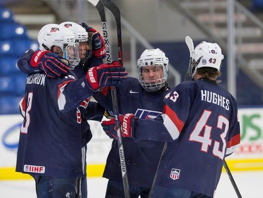 Members of the U.S. NTDP Under-18 team celebrate one
