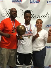 Rickie Wedlow, center, poses with his parents, Rick, left, and Tawanda after Wedlow's AAU team won the USBA seventh grade National Championship in Atlanta, Georgia, last summer.