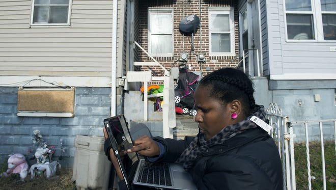 Inspector Toy Humes enters code violations into her laptop outside a home in North Camden.