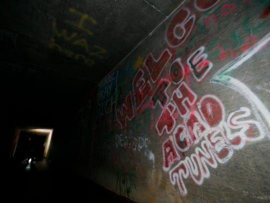"""Graffiti saying """"Welcome to the Acid Tunnel"""" greets"""
