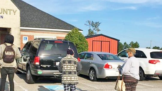 Spaced six feet apart, a crowd of people line up outside the Barnwell County Voter Registration & Elections office on Oct. 5, the first day of absentee voting in South Carolina.