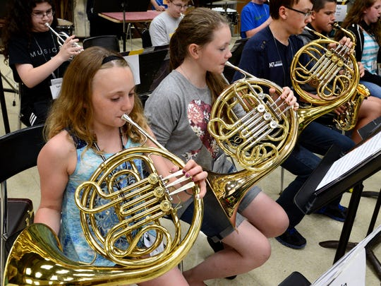 Erin Popies, left, Anna Gorski, center, and William Dewey play French horn at seventh and eighth grade band rehearsal during summer music camp at the University of Wisconsin-Green Bay on Thursday.