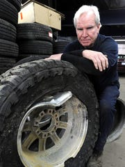 Chris Lynch of Wetmore's Auto and Tire in Ferndale displays a tire damaged by Michigan's pothole-marked roads in 2018.