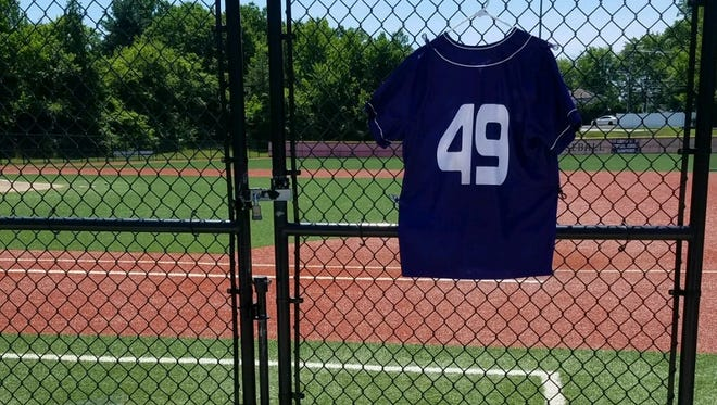Daniel Vincent DiMino Jr., so of Old Bridge athletics director Dan DiMino, leaves a bouquet of flowers at the high school baseball field beneath Zach Attainese's game jersey.