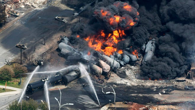 Smoke rises from railway cars carrying crude oil after derailing July 6, 2013, in downtown Lac Megantic, Quebec. The U.S. Federal Railroad Administration is urging railroads to share more information about inspections and maintenance, to build confidence in local officials concerned about aging bridges and tunnels.