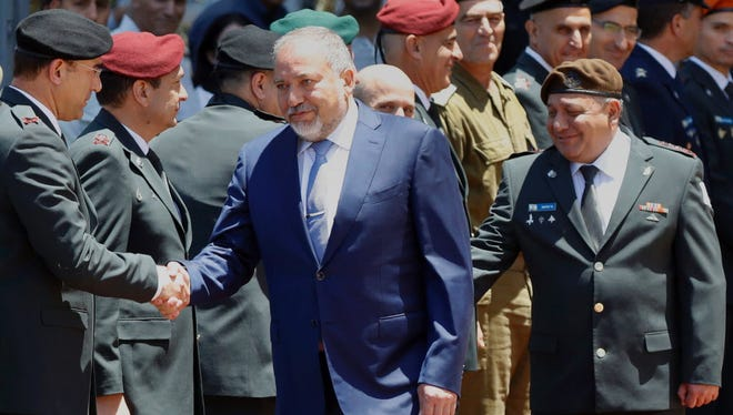 "Israeli Defense Minister Avigdor Lieberman, center, condemns a truce in Gaza as a ""surrender to terror."""
