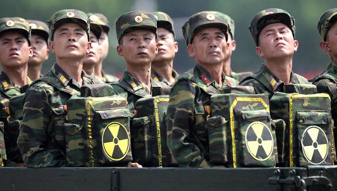North Korean soldiers turn and look toward their leader Kim Jong Un during a ceremony marking the 60th anniversary of the Korean War armistice on July 27, 2013.