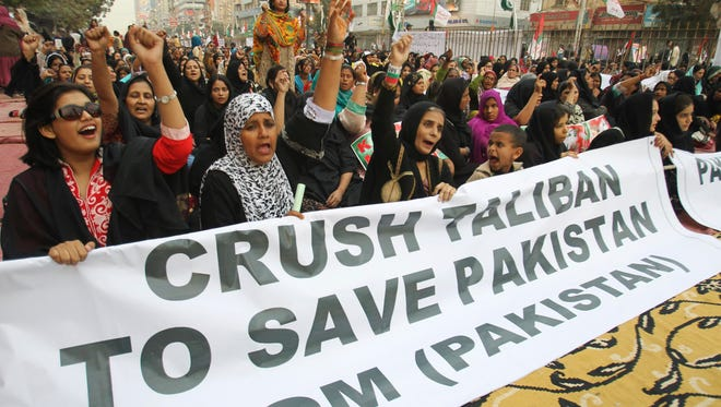 Supporters of Pakistan's political party Muttahida Qaumi Movement express solidarity with families of the students killed in Tuesday's Taliban attack on a military-run school in Peshawar, as they rally in Karachi, Pakistan, Friday, Dec. 19, 2014.