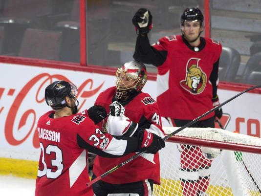 Ottawa Senators goalie Craig Anderson, center, is congratulated by defenseman Fredrik Claesson as defenseman Chris Wideman skates past the net at the end of third-period NHL hockey game action against the Detroit Red Wings, Thursday, Nov. 2, 2017, in Ottawa, Ontario. (Adrian Wyld/The Canadian Press via AP)