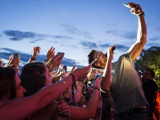 Jake Owen takes a selfie with fans in the crowd as