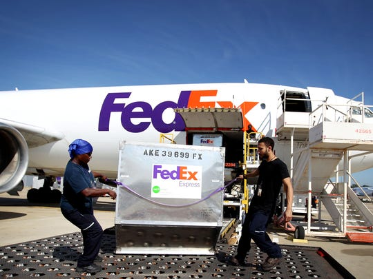 Maronda Harris, left, and Michael Figlewicz off-load shipping containers from an air freighter at the FedEx Memphis World Hub in 2015.