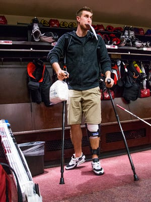 Arizona Coyotes defenseman Michael Stone hobbles on crutches as he leaves his locker at Gila River Arena as the NHL season has come to an end for the team. Stone was injured during the season.