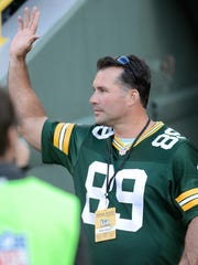 Mark Chmura waves to the crowd as he is introduced at halftime. The Green Bay Packers welcomed their alumni back for their game against the New York Jets at Lambeau Field on Sunday, Sept. 14, 2014.