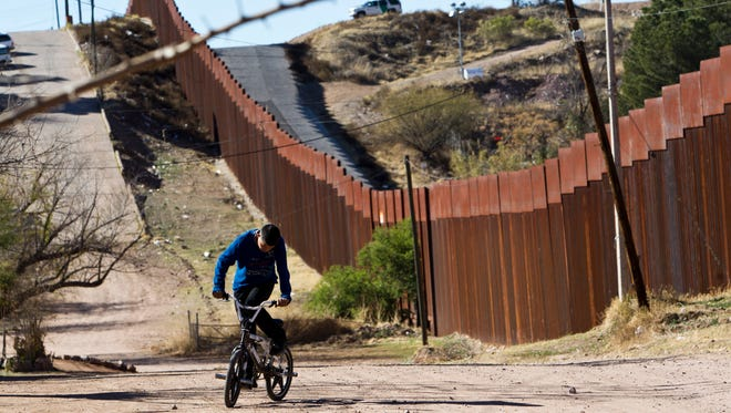 A youth rides along Calle Internacional, on the east side of Nogales, Sonora. The low section of the fence behind him is one of the busiest crossing spots for migrants and drugs in the area, residents and Border Patrol agents say.