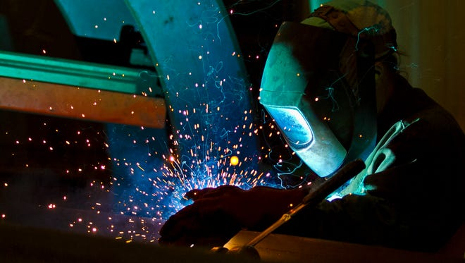 Kathy Campbell, a welder at Dean Steel Buidings in Fort Myers, works on a rafter beam at the manufacturing facility.