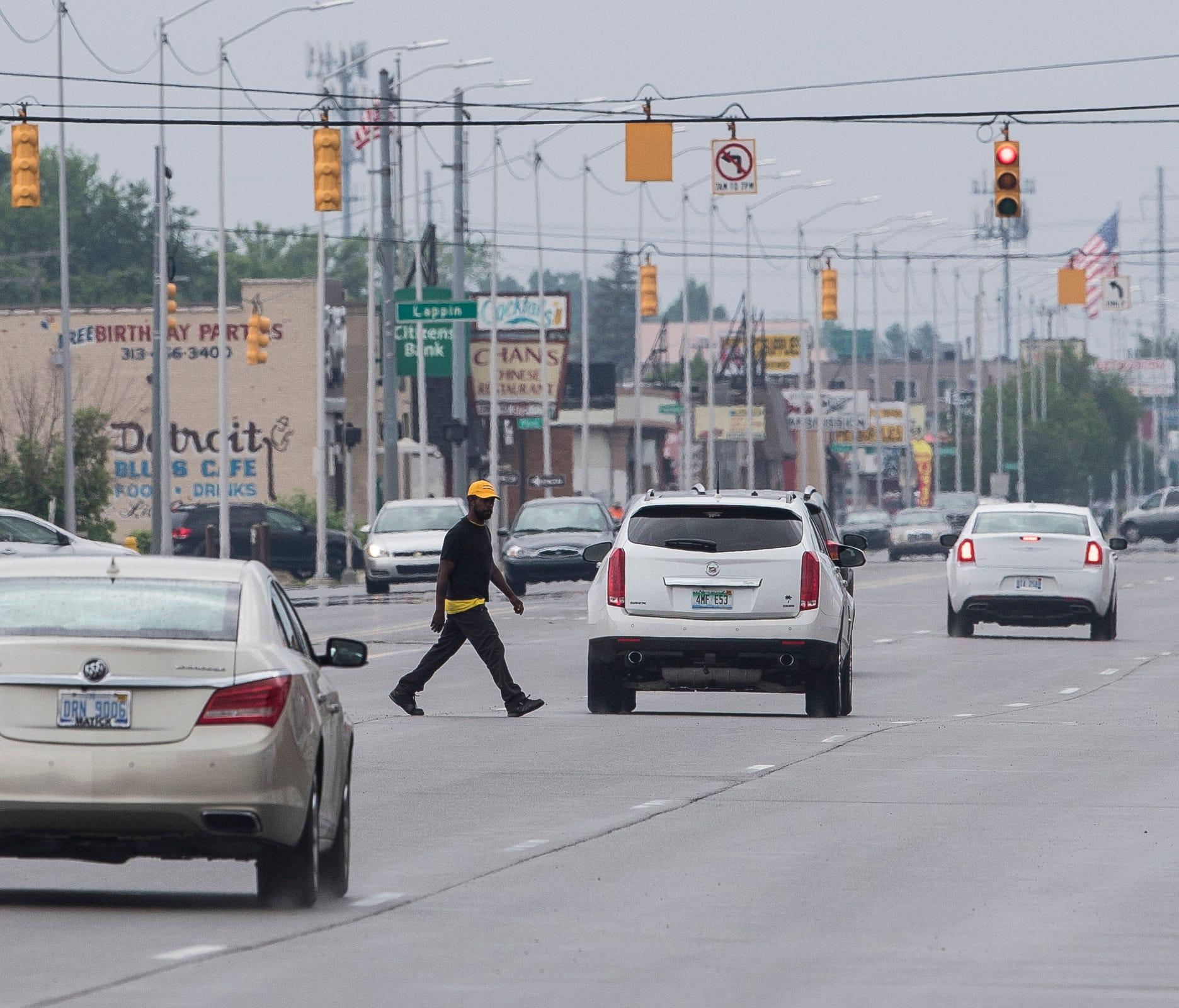 A man is seen crossing Gratiot Avenue near Greiner Street in Detroit, Saturday, June 9, 2018.