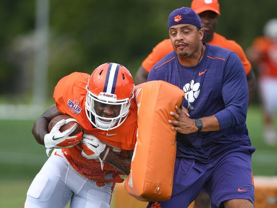 Clemson co-offensive coordinator Tony Elliott hits running back Tavien Feaster (28) with a pad during a drill at the Tigers practice on Tuesday, August 8, 2017.