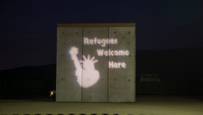 """Activists in Tijuana, Mexico, protest President Donald Trump's proposed border wall by projecting an image of the Statue of Liberty with the words """"Refugees Welcome Here"""" onto one of the prototypes on Nov. 18, 2017."""