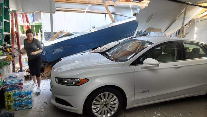 Courtney Piana of Mt. Lookout walks in her garage past her new 2016 Ford Fusion which was narrowly missed by the boom of a crane that collapsed while lifting sections of a downed tree from her backyard.