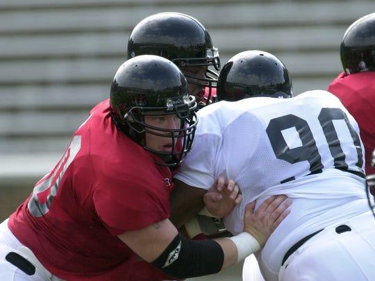Then-Bearcat Doug Rosfeld works on blocking UC teammate Mario Monds during team play at Nippert Stadium
