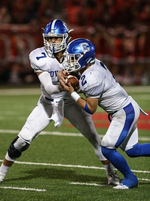 Covington Catholic quarterback AJ Mayer hands off to Casey McGinness during their game at Beechwood, Friday, September 15, 2017.