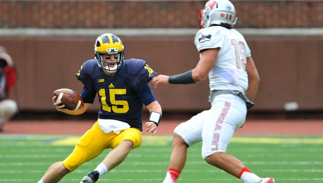 Michigan Wolverines quarterback Jake Rudock tucks the ball and runs on third and long in the second quarter against UNLV.