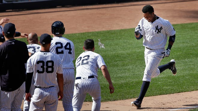 The New York Yankees await Starlin Castro as he approaches home plate after hitting a walk-off home run against the Colorado Rockies in the ninth inning of a baseball game, Wednesday, June 22, 2016, in New York. The Yankees won 9-8.