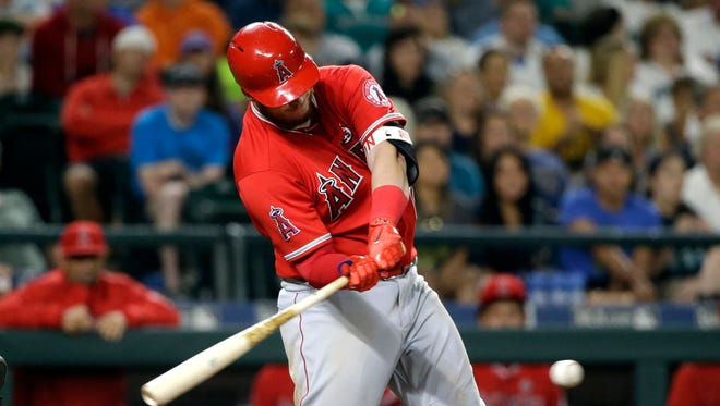 Los Angeles Angels' C.J. Cron hits a grounder that resulted in a run on an error by the Seattle Mariners during the ninth inning of the Angels' 6-5 win on Friday.