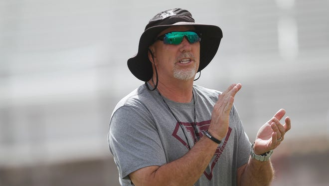Hamilton head coach Steve Belles runs drills as the Hamilton High School football team practices on Monday, April 25, 2016, in Chandler, Ariz.